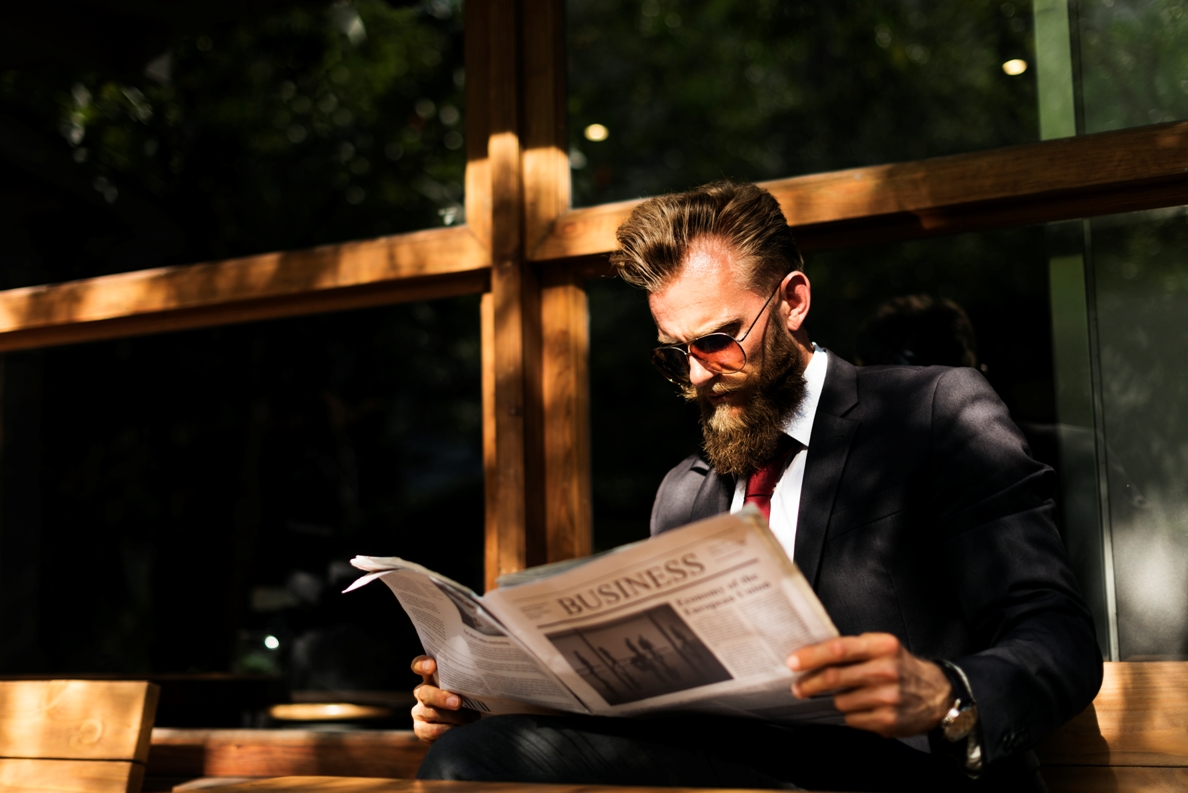 Businessman reading newspaper at coffee shop